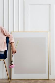 Femme tenant une fleur assise près d'un cadre
