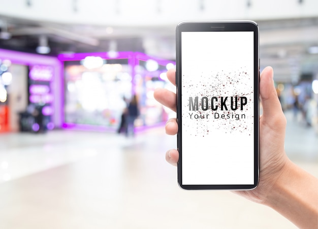 Femme tenant une main et touchant un smartphone noir avec une maquette d'écran blanc pour votre conception sur le grand magasin abstrait flou ou un centre commercial.