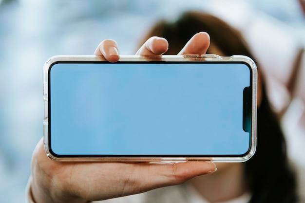 Femme tenant une maquette d'écran de téléphone portable