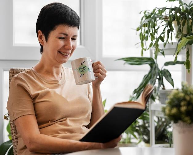 Femme tenant une maquette de mug dans son verger urbain