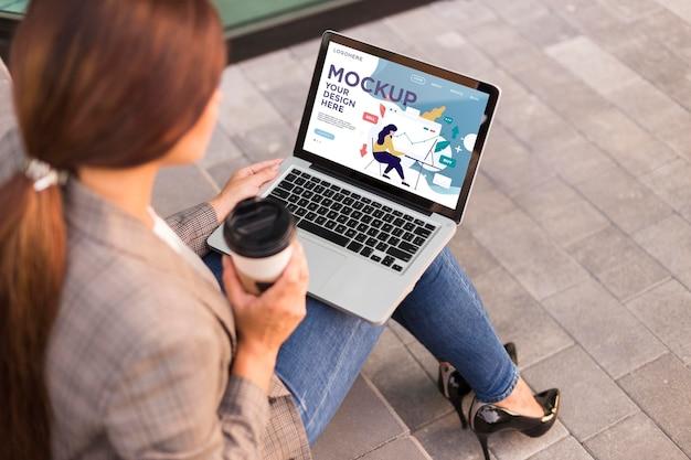 Femme tenant une maquette d'ordinateur portable à l'extérieur
