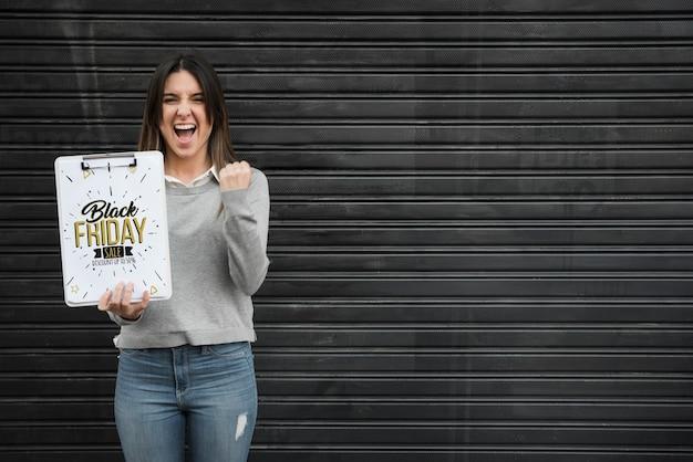 Femme tenant une maquette de presse-papiers avec concept de vendredi noir