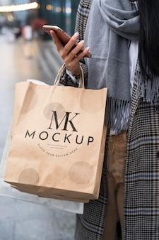 Femme tenant des sacs à provisions et téléphone