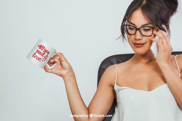 Une femme tenant une tasse de café se moque et fait un appel téléphonique