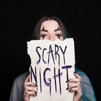Femme vampire tenant un papier avec lettrage