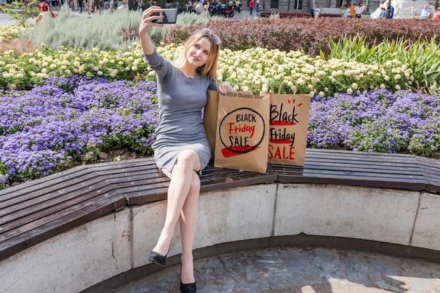 Femme en ville avec des sacs de vendredi noir