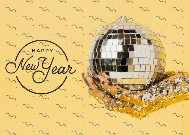 Femme vue de face tenant une boule disco avec lettrage du nouvel an