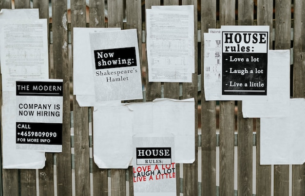 Feuilles de papier annonces sur une clôture en bois