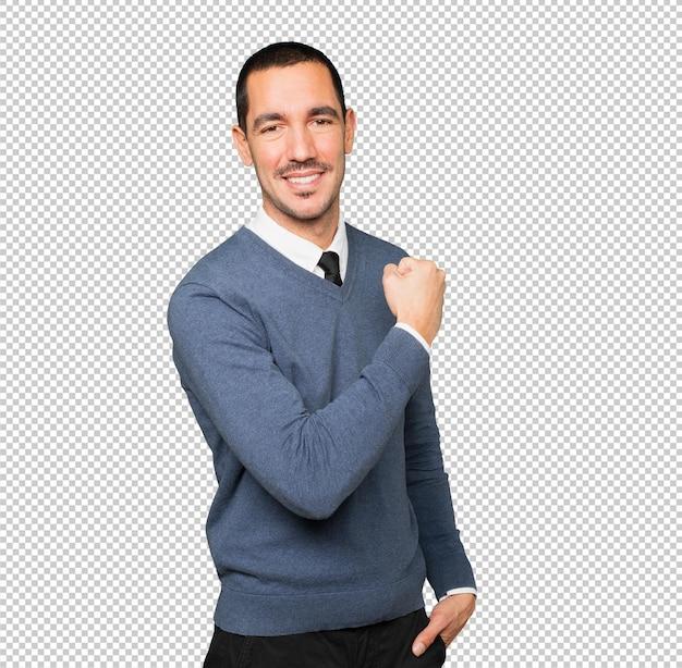 Fier jeune homme faisant un geste de force avec son bras