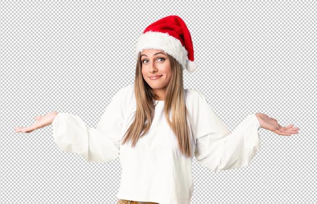 Fille blonde avec un chapeau de noël ayant des doutes et avec une expression du visage confuse