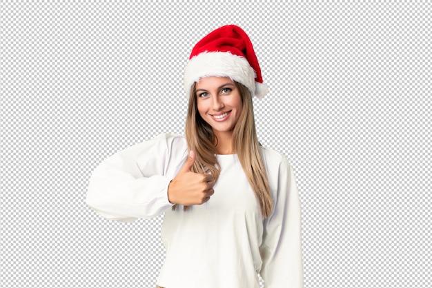 Fille blonde avec un chapeau de noël donnant un geste du pouce levé