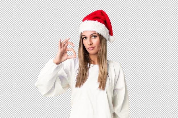Fille blonde avec un chapeau de noël montrant un signe ok avec les doigts