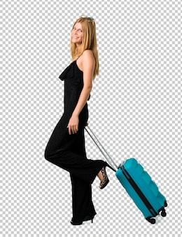 Fille blonde voyageant avec sa valise à pied