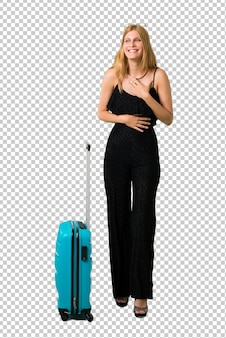 Fille blonde voyageant avec sa valise souriant beaucoup en mettant les mains sur la poitrine