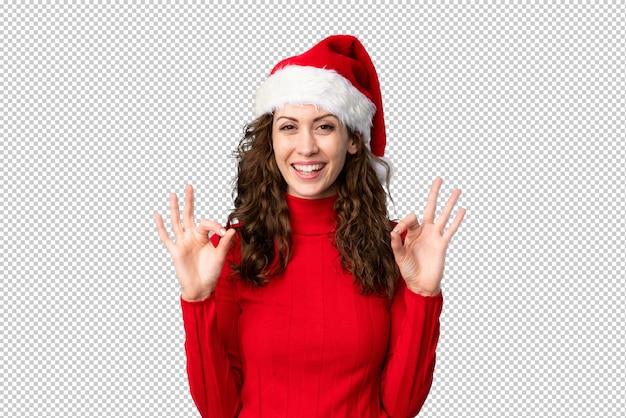 Fille avec un chapeau de noël montrant un signe ok avec les doigts