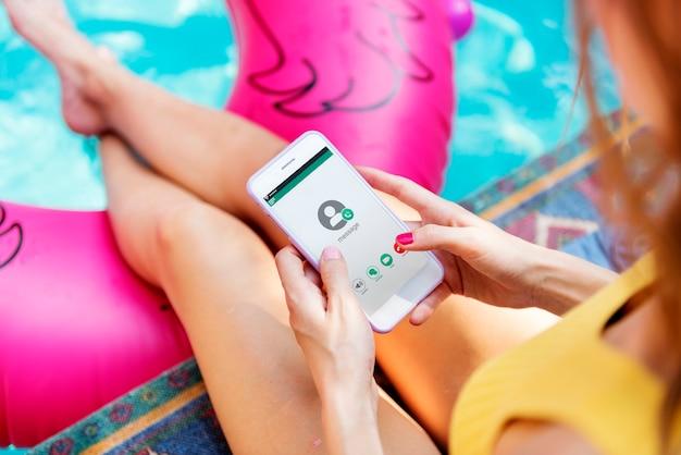 Fille jouant au téléphone au bord de la piscine