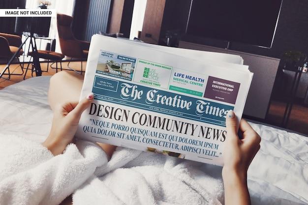 Fille sur le lit lisant la maquette du journal