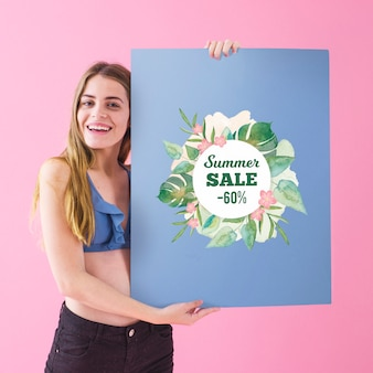 Fille montrant l'affiche de vente d'été