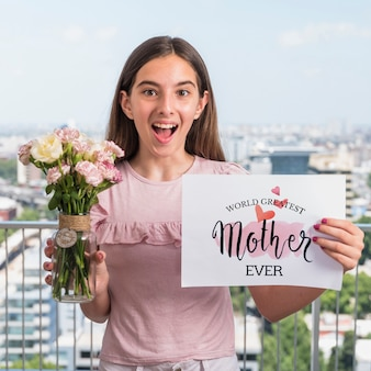Fille présentant une maquette en papier pour la fête des mères