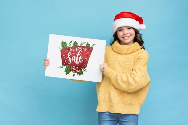 Fille souriante tenant une feuille de papier avec un message de vente