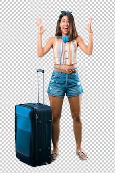 Fille voyageant avec sa valise avec une expression faciale surprise et choquée.