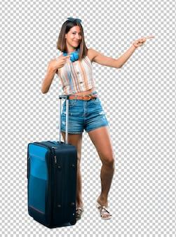 Fille voyageant avec sa valise pointant le doigt sur le côté et présentant un produit en souriant