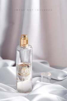 Flacon de parfum luxueux sur un tissu de soie drapé dans des tons gris