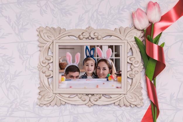 Fleurs à côté du cadre avec photo de famille de pâques