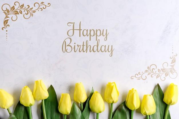 Fleurs de tulipe jaune joyeux anniversaire sur fond de pierre, mise à plat avec espace copie