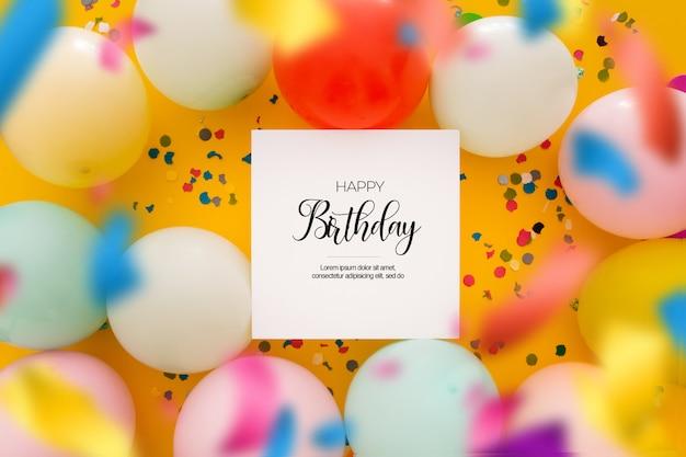 Fond d'anniversaire avec des confettis flous et des ballons sur jaune