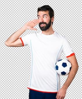 Footballeur tenant un ballon de foot en écoutant quelque chose
