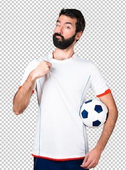 Footballeur tenant un ballon de football fier de lui-même