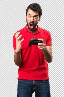 Frustré beau jeune homme jouant à des jeux vidéo