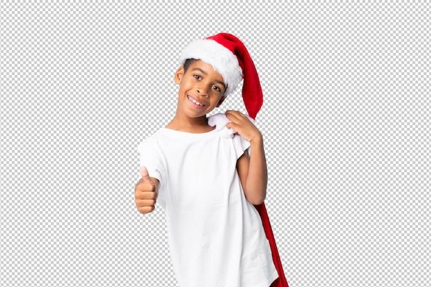 Garçon afro-américain avec chapeau de noël et prenant un sac avec des cadeaux et avec le pouce vers le haut