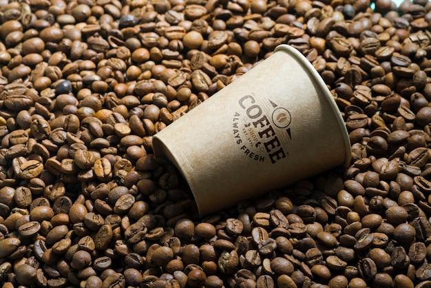 Grains de café aromatiques et tasse de maquette en papier.