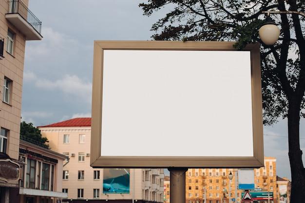 Un grand panneau d'affichage avec des informations intéressantes et de la publicité installé le long d'une large rue du centre-ville