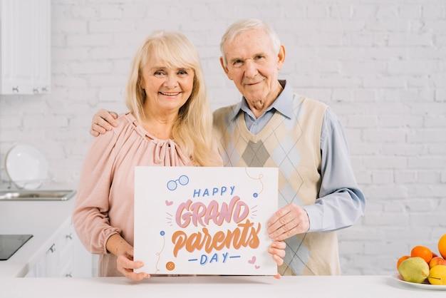 Grands-parents tenant la maquette de la pancarte