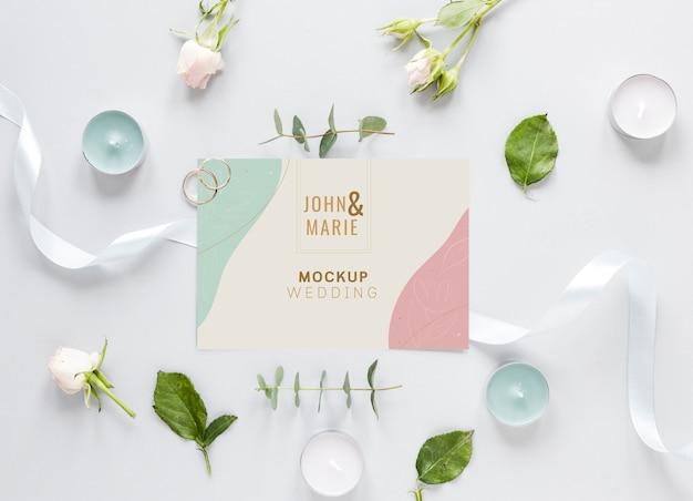 Gros plan de carte de mariage avec bougies et fleurs