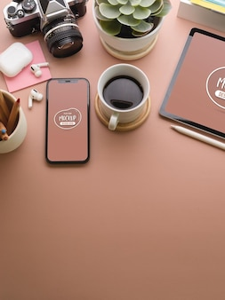 Gros plan de l'espace de travail créatif rose avec maquette de smartphone