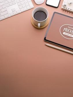 Gros plan de l'espace de travail rose avec maquette de tablette numérique