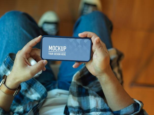 Gros plan d'homme d'affaires tenant une maquette de smartphone horizontal