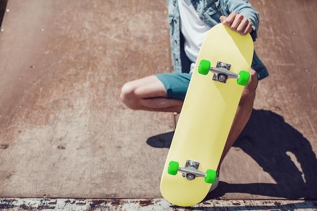 Gros plan sur le jeune homme tenant une maquette de planche à roulettes
