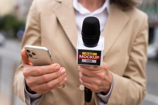 Gros plan sur un journaliste tenant une maquette de microphone