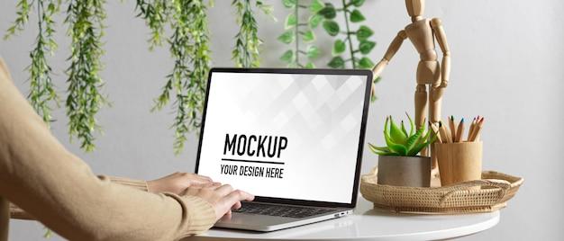 Gros plan sur la main féminine à l'aide d'une maquette d'ordinateur portable