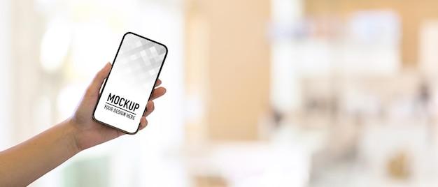 Gros plan de la main de femme tenant le smartphone et montrant l'écran de maquette