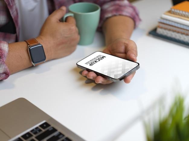 Gros plan de la main de l'homme d'affaires à l'aide de la maquette de smartphone