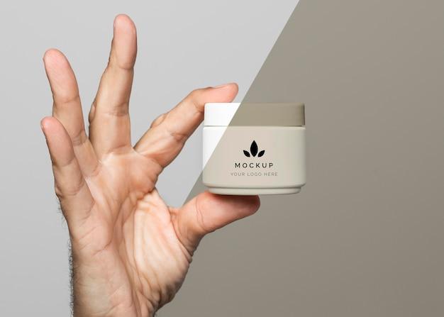 Gros plan de la main avec récipient de crème