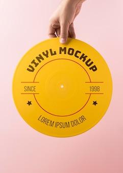 Gros plan main tenant une maquette de vinyle jaune