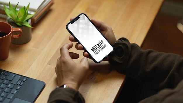 Gros plan des mains mâles à l'aide de la maquette de smartphone