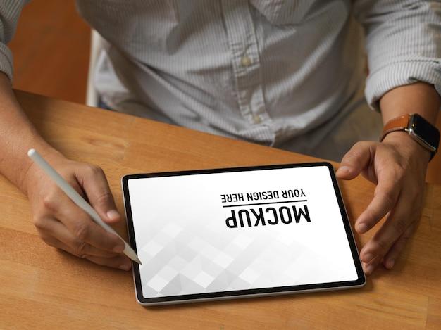 Gros plan des mains mâles à l'aide de tablette de maquette numérique sur table en bois